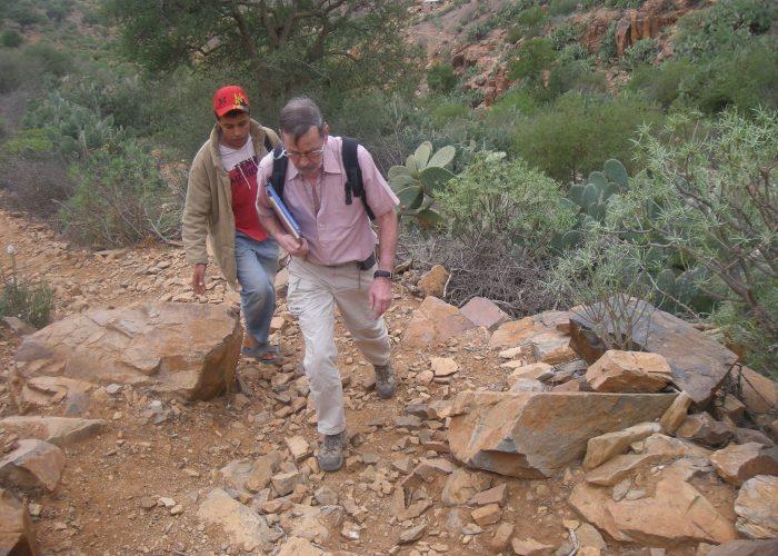 L'hydrogéologue visite le village pour trouver l'endroit le plus propice à la construction du puits.