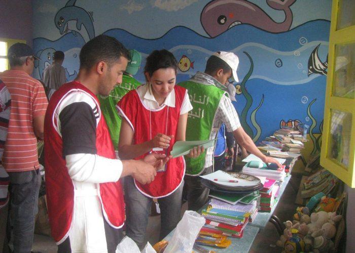 Les bénévoles s'apprêtent à distribuer les fournitures scolaires aux enfants.