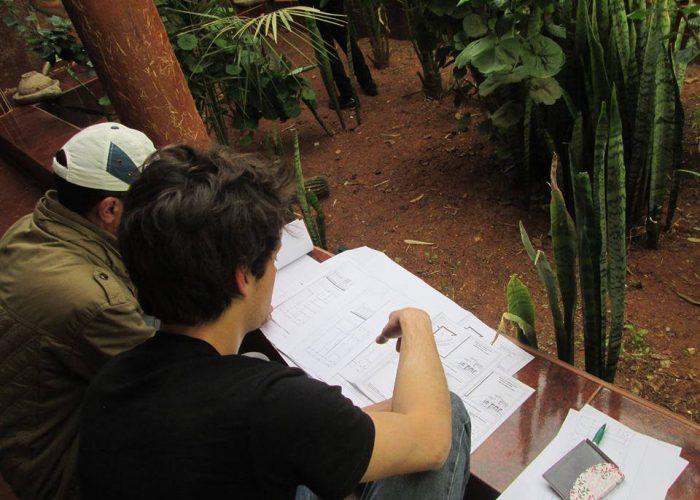 L'architecte bénévole de BackUp Rural vérifie les plans de la coopérative avec le constructeur