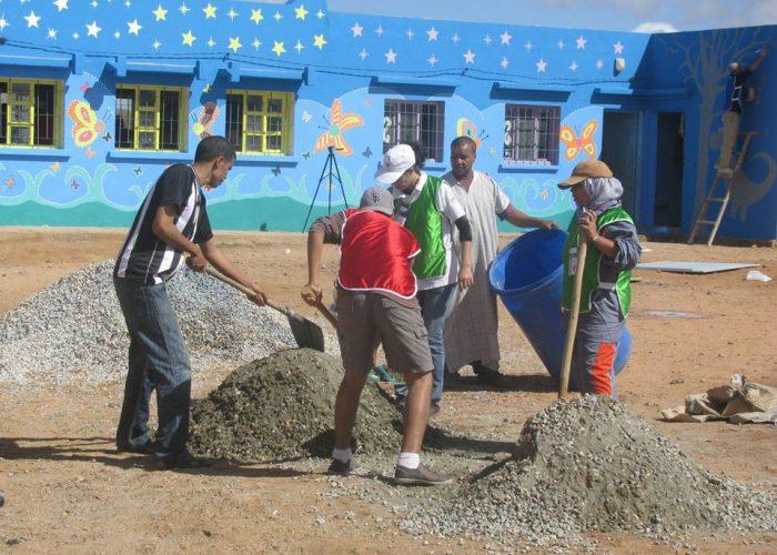 Les bénévoles nivèlent le terrain et creusent des trous pour planter des arbres.