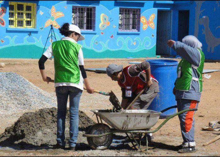 Les bénévoles coulent une dalle de béton.